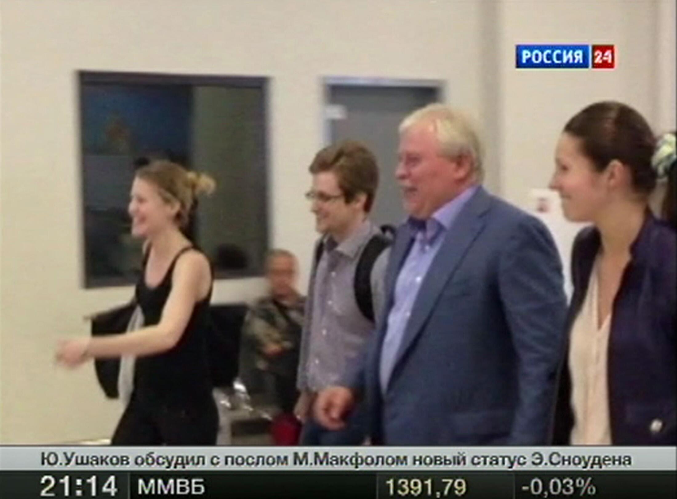 Capture d'écran d'une télévision russe où l'on voit Edward Snowden (2e à gauche) quitter la zone de transit de l'aéroport Cheremetievo, accompagné par son avocat, après avoir obtenu le droit d'asile. Moscou, le 1er août 2013.