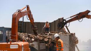 Des ouvriers sur le chantier de démolition de l'ancien siège du PND, le parti de l'ex-président Moubarak, au Caire le 31 mai 2015.