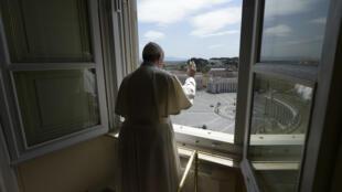 El papa Francisco se asoma a una desierta plaza de San Pedro desde la ventana del palacio Apostólico tras el rezo del Ángelus dominical, emitido por Internet desde la biblioteca palaciega, el 10 de mayo de 2020 en el Vaticano