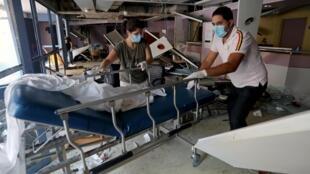 Des employés déplacent un lit dans un hôpital endommagé après l'explosion de mardi à Beyrouth, le 5 août 2020.