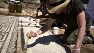 Un arqueólogo trabaja sobre un mosaico en el sitio arqueológico de Sainte-Colombe, en el este de Francia.