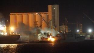Cảnh tàu bốc cháy ở cảng Tripoli sau đợt oanh kích của NATO đêm 19 rạng sáng 20/05/2011 theo giải thích của chính quynề Libya