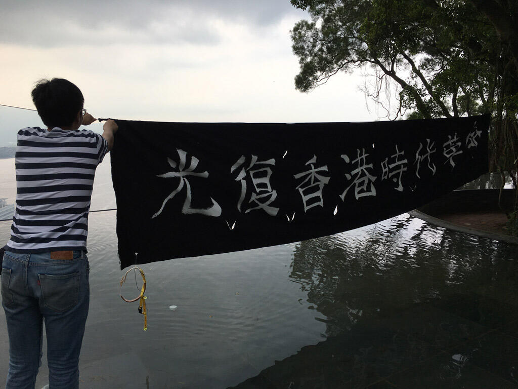 Mike next to a banner carrying his favourite slogan: « Retake Hong-Kong. Revolution of our times ».