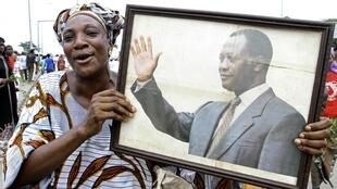 A woman holds a portrait of Alassane Ouattaraduring a demonstration in Abobo, 8 March 2011