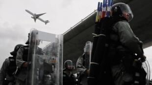 存檔圖片 Image d'archive: Un avion survole la police anti-émeute lors de la protestation contre le projet de loi anti-extradition à l'extérieur de l'aéroport de Hong Kong, Chine, le 1er septembre 2019.