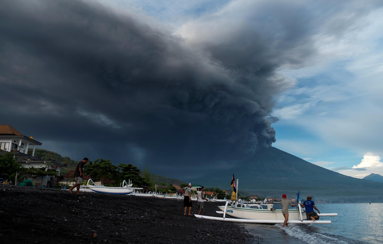 Nuvens de fumo significando a iminente erupção do vulcão do Monte Agung,levam  pescadores da região  de Amed a  escapar  de barco. 26 de Novembro  de 2017
