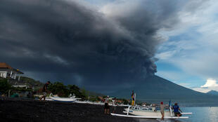 Indonesia's Mount Agung volcano erupts as fishermen pull a boat onto the beach in Amed, Bali, Indonesia, November 26, 2017.