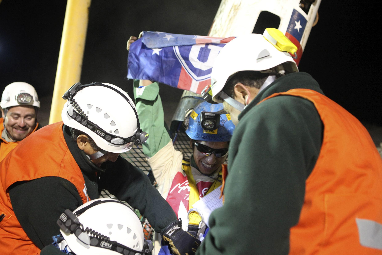 O mineiro Jimmy Sánchez agita a bandeira do seu clube de futebol Universidad de Chile ao ser resgatado.