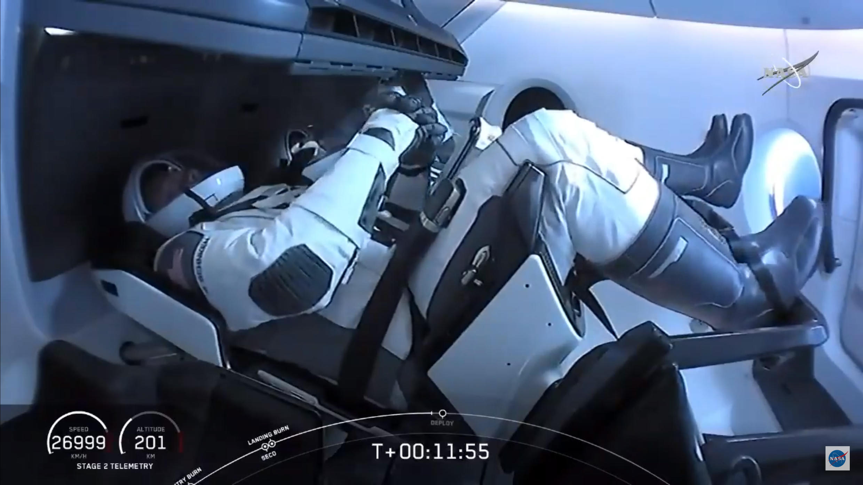 Los astronautas Bob Behnken (en primer término) y Doug Hurley , en el interior de la cápsula Crew Dragon deSpaceX, el 30 de mayo de 2020 tras el lanzamiento desde Cabo Cañaveral (sureste de EEUU), en una imagen tomada de la televisión de la NASA