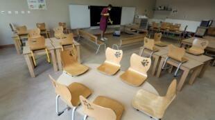 Un employé nettoie une salle de classe d'une école primaire pour la rentrée scolaire qui aura lieu le mardi 1er septembre en France.