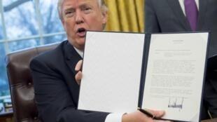 Presidente americano, Donald Trump exibindo o decreto de retirada dos Estados Unidos do acordo de parceria transpacífico;