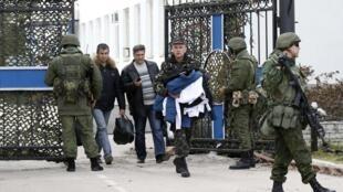 Các sĩ quan hải quân Ukraina khăn gói hành lý rời tổng hành dinh lực lượng hải quân tại Sebastopol-Crimée trước sự áp giải của nhóm vũ trang, ngày 19/3/2014.