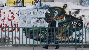 A Hamas policeman walks past a mural depicting an exploded Israeli tank, in Gaza City, 22 November