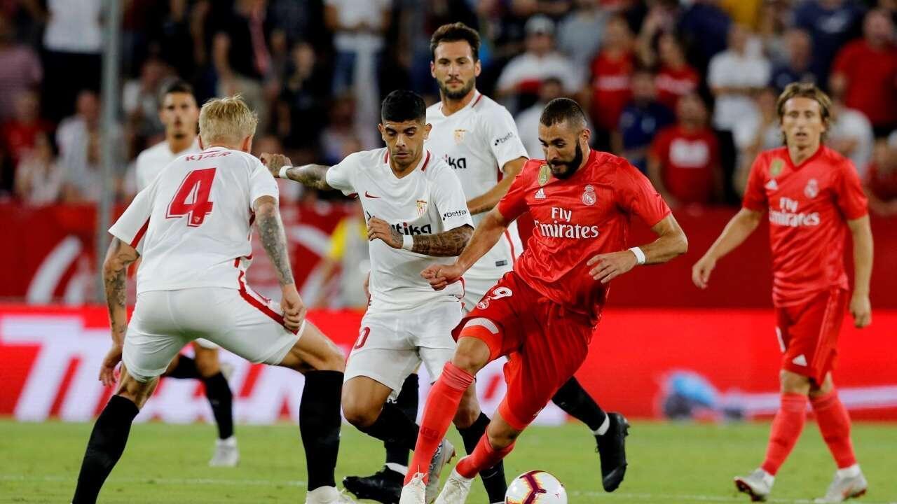 Dan wasan gaba na kungiyar Real Madrid Karim Benzema, yayinda yake kokarin kurdawa tsakanin 'yan baya na Sevilla.