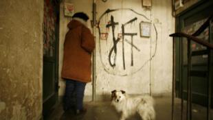 Une femme âgée entre dans son appartement  à Pékin avec un signe peint sur le mur annonçant la démolition dans quelques semaines.
