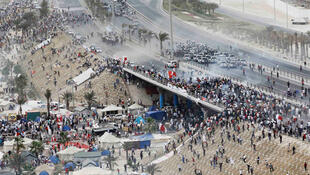 Anti-government protesters confront riot police assembled on a flyover near the Pearl Square in Manama