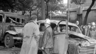 Paris, le 15 juillet 1953. Des pompiers s'affairent près d'une voiture particulière et d'un car de police incendiés au cours d'affrontements entre manifestants algériens et policiers qui ont éclaté la veille.