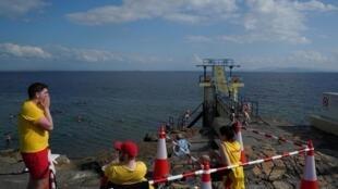 Des sauveteurs en mer surveillent le plongeoir, inaccessible à cause du Covid-19, sur la plage à Galway en Irlande, le 11 août 2020.