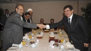 Iran's Parliament speaker Ali Larijani (L) shakes hands with Turkey's Foreign Minister Ahmet Davutoglu