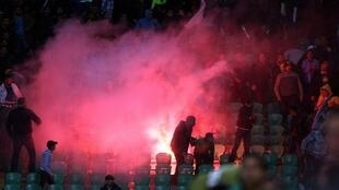 Flares are thrown in the stadium during clashes that erupted after a football match between Egypt's Al-Ahly and Al-Masry teams
