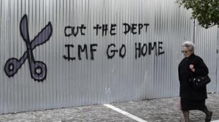 """Mensagem em um muro da capital Atenas, em imagem registrada um dia antes das eleições legislativas na Grécia, diz: """"Acabe com a dívida. FMI vá embora""""."""