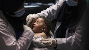 A nurse holds five-month-old Omar al-Hadidi who was pulled alive from under the rubble of a home hit by an Israeli air strike in Gaza while his mother and four siblings were killed