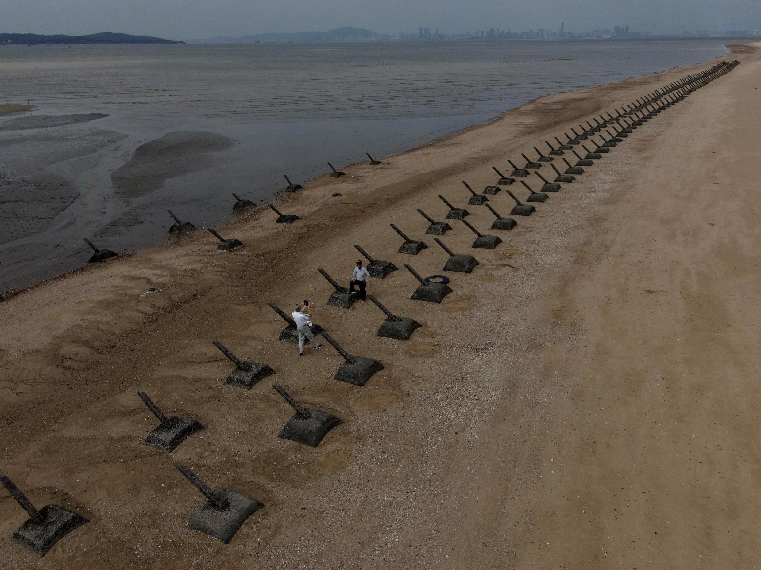 Anti-landing spikes line a beach in Taiwan's Kinmen, with mainland China visible in the background