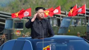 Hoton shugaban Korea ta Arewa  Kim Jong Un  yayin da yake kallon wani atasaye na soja.