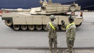 Soldados americanos acompanham a chegada no porto de Riga de um tanque Abrams, das tropas dos EUA, em 9 de março de 2015.