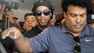 L'ex-star du football brésilien Ronaldinho encadré par des policiers paraguayens à Assomption le 5 mars 2020.