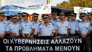 Manifestation anti-gouvernementale à Salonique, le 10 septembre 2010, où des policiers grecs tiennent une banderolle où l'on peut lire « les gouvernements changent  mais les problèmes restent ».