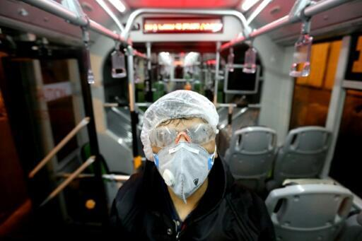 A city council worker in protective clothing disinfects a bus in Tehran as part of government efforts to control a novel coronavirus outbreak that has now killed 19 people