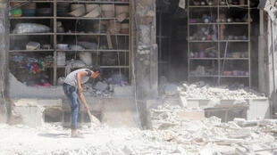 Un jóven remueve escombros frente a una tienda fuertemente dañada por un bombardeo aéreo en una zona rebelde de Alepo. Este 18 de agosto de 2016.