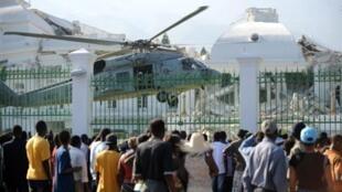 La population regarde atterrir un hélicoptère de la marine américaine en face du palais présidentiel endommagé, à Port-au-Prince, le 19 janvier 2010.