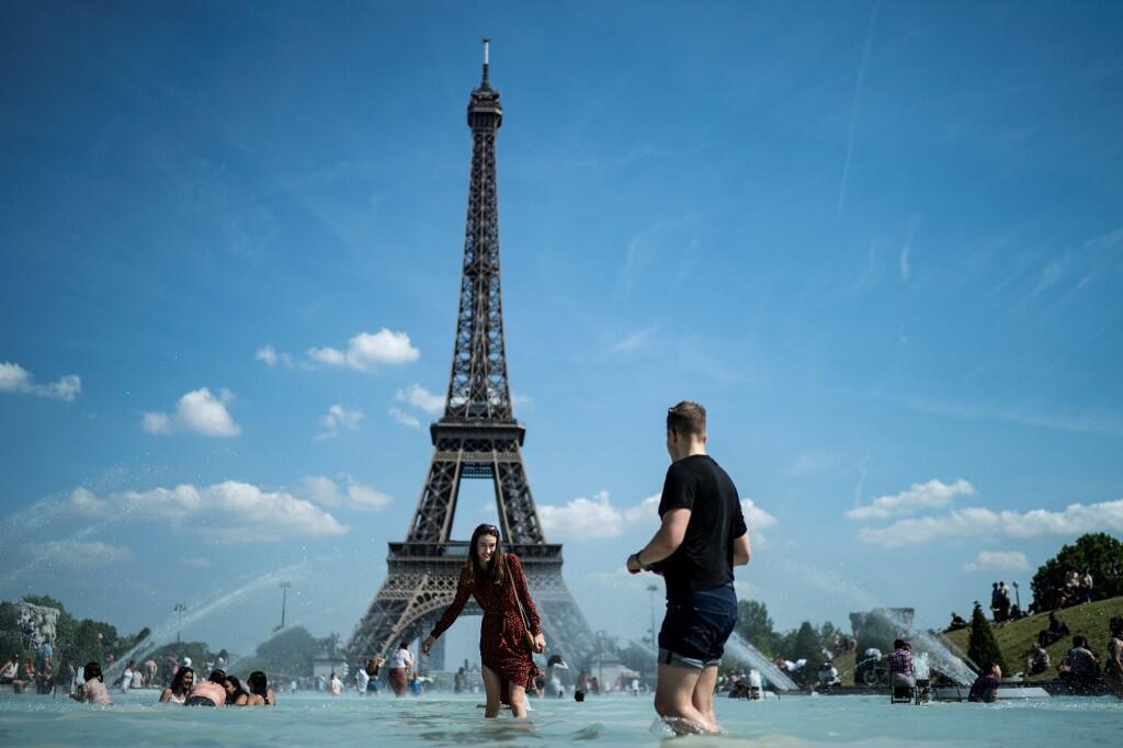 A couple play with water as they cool themselves down in the fountain of the Trocadero esplanade in Paris on June 25, 2019 with the Eiffel Tower on the background. Forecasters say Europeans will feel sizzling heat this week with temperatures soaring as hig