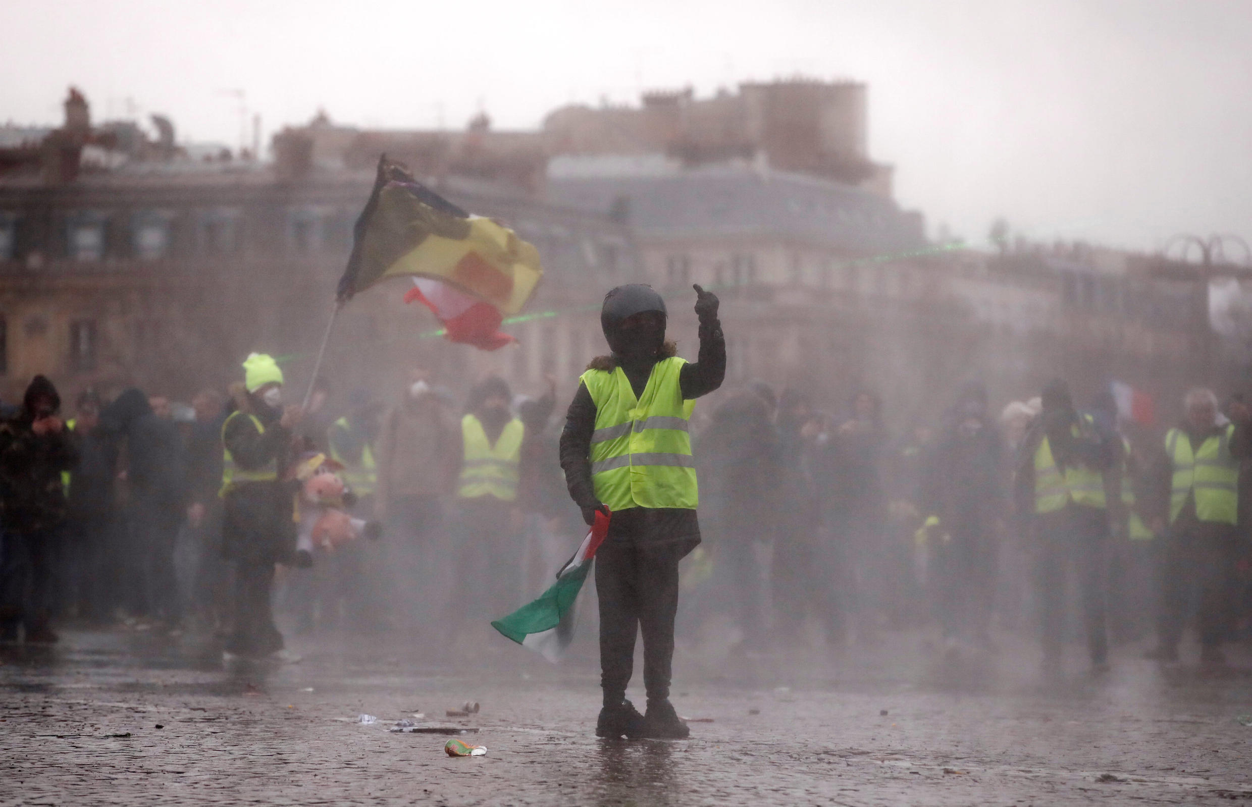 """A protester wearing a yellow vest gestures during a demonstration by the """"yellow vests"""" movement near the Arc de Triomphe in Paris, France, January 12, 2019."""