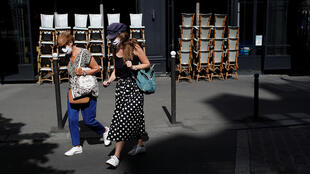 Women wearing protective face masks walk past a Paris restaurant, which remain closed after France began slowly lifting confinement measures on 11 May.