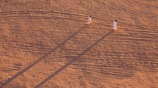 两名移民行走在一望无际的苏丹沙漠