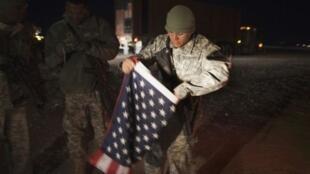 Un soldado estadounidense pliega la bandera de su país antes de salir definitivamente de Irak.