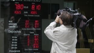 Devant un tableau de change des devises, à Buenos Aires, le 24 janvier 2014.