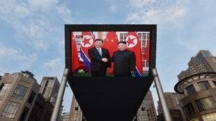 A giant television screen in Beijing shows the arrival of China's president Xi Jinping in Pyongyang, June 20, 2019.
