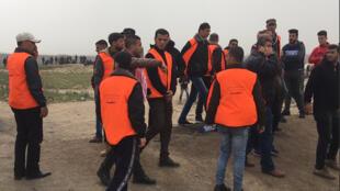 Des militants floqués d'un gilet orange ont assuré le service d'ordre, à l'appel du comité d'organisation de la Grande marche du retour, à Gaza, le 30 mars 2019.