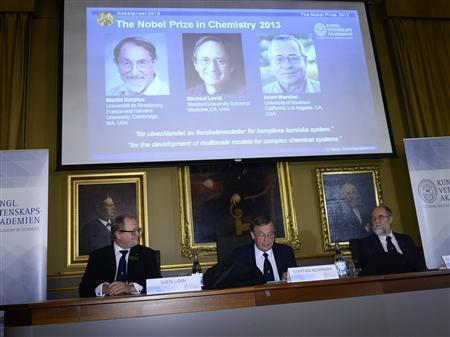 Trên màn hình: Ảnh các nhà khoa học Karplus, Levitt và Warshel đoạt giải Nobel Hóa học 2013
