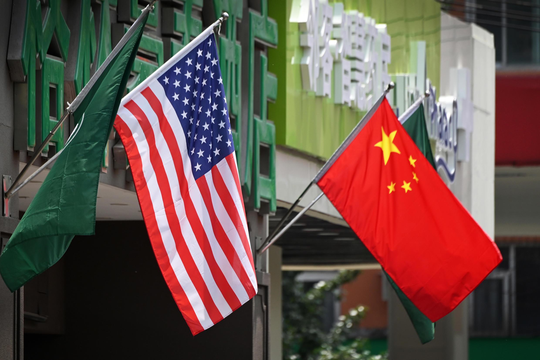 Una banrdea china y una estadounidense ondean el 14 de mayo de 2019 en un hotel de Pekín