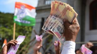 Les partisans indiens du Parti du Congrès tiennent des billets de monnaie indiennes pendant une protestation contre la décision de demonitiser les billets de 500 et 1000INR à Bangalore, le 28 novembre 2016.