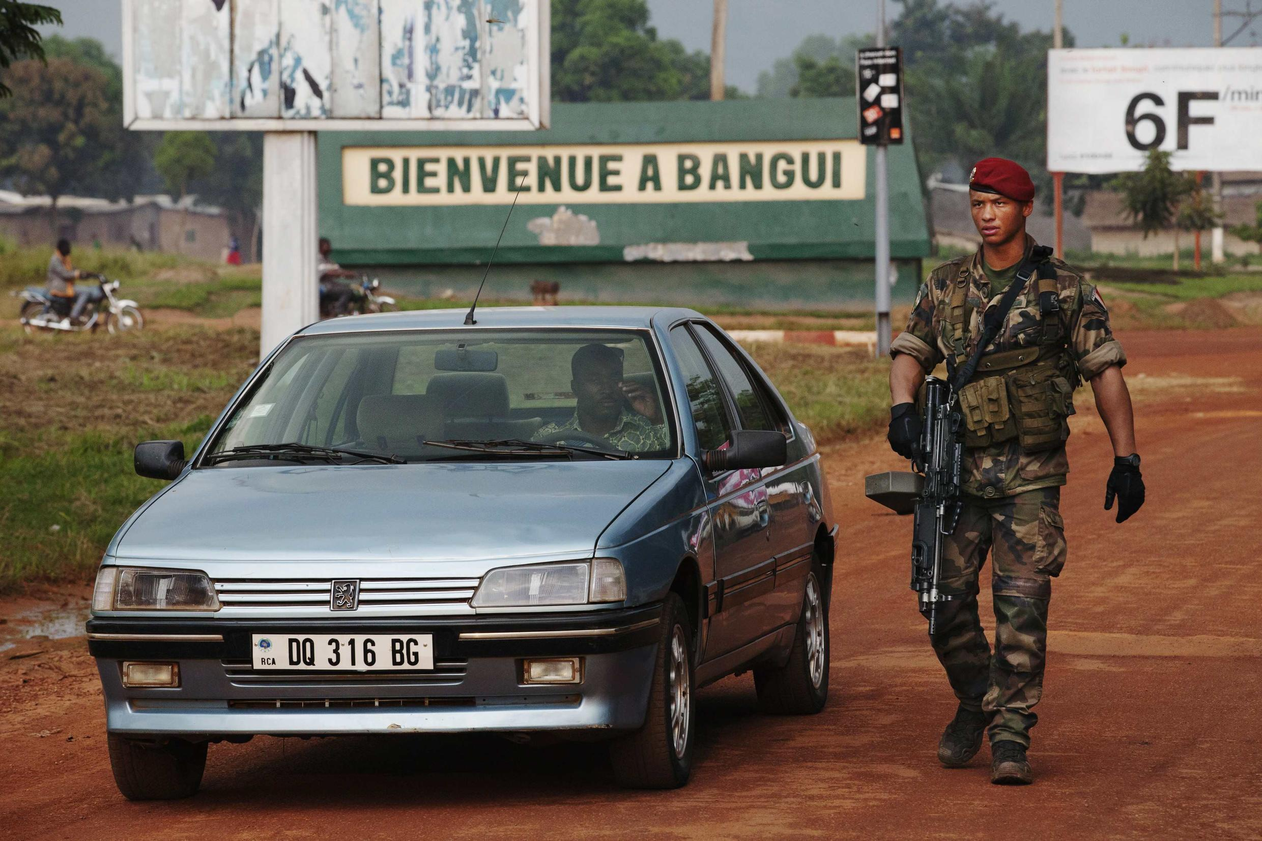 A French soldier inspects a car at a checkpoint at the Mpoko airport in Bangui