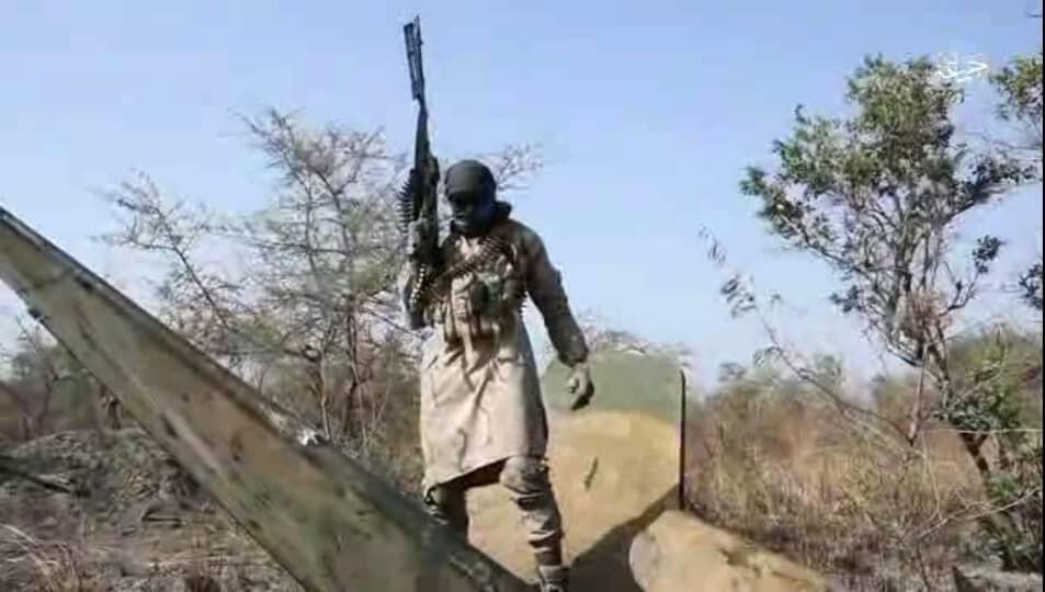 Wani mayakin Boko Haram a cikin hoton bidiyon da kungiyar ta fitar, tsaye kan abinda ake zaton baraguzan jirgin yakin Najeriya ne.