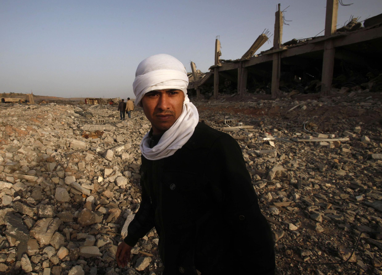 Un hombre camina sobre los escombros de un depósito de armas destruido cerca de Benghazi .