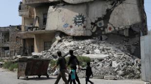 Người dân Syria đi ngang qua một tòa nhà bị hư hại có hình minh họa virus corona, tại thành phố Idleb do phe nổi dậy kiểm soát, ngày 18/04/2020.