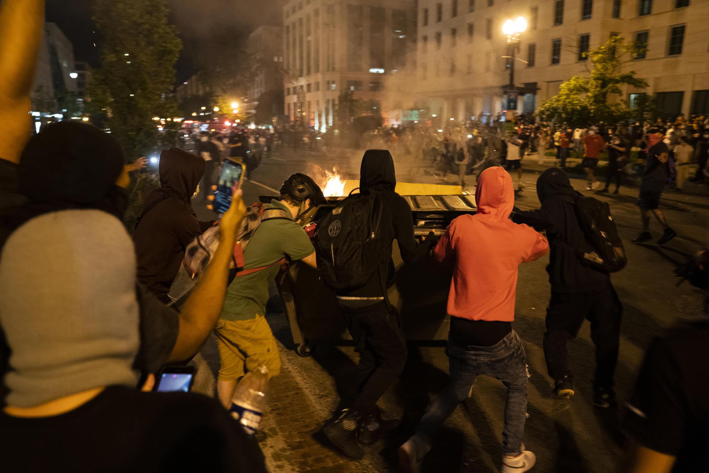 Manifestantes queimam lixeiras diante de policiais, em protesto próximo à Casa Branca no dia 30 de maio de 2020.